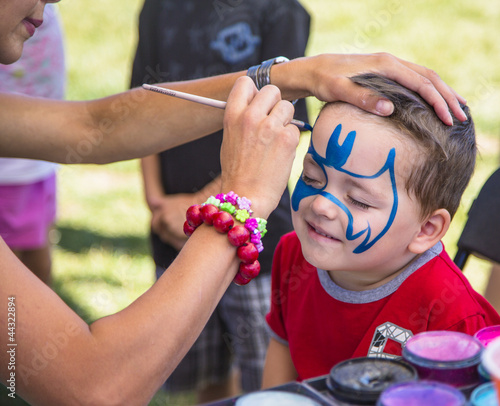 young boy getting his face painted