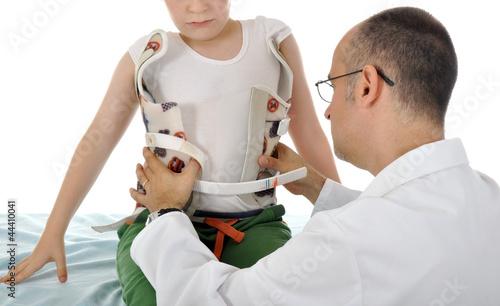 Photographie Arzt behandelt Kind mit Stützkorsett