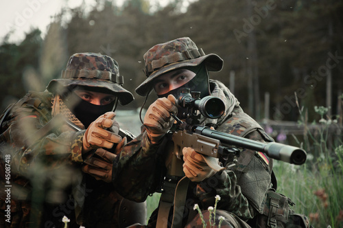 Obraz na plátně Soldiers snipers attack the enemy from a secured building