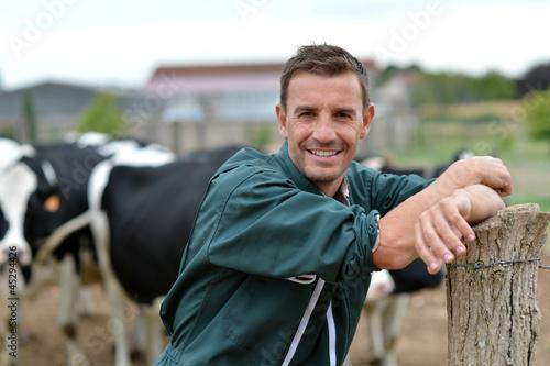 Fotografia Herdsman standing in front of cattle in farm