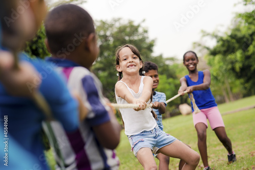 Happy school children playing tug of war with rope in park #45849681