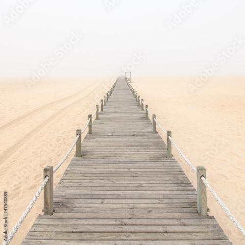 Wooden footbridge on a foggy sand beach background. Portugal.