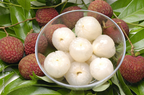 Bowl of peeled lychee on leaf background