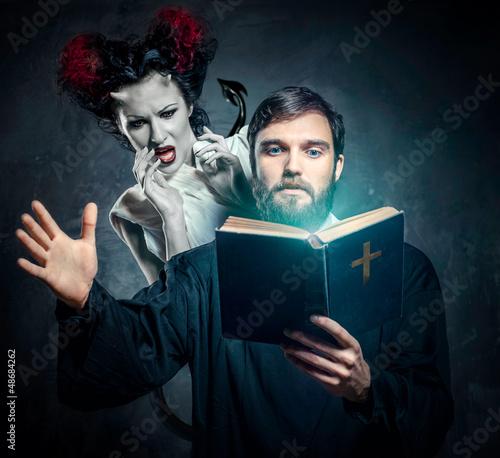 Priest evicting demons, conceptual photo Fototapeta