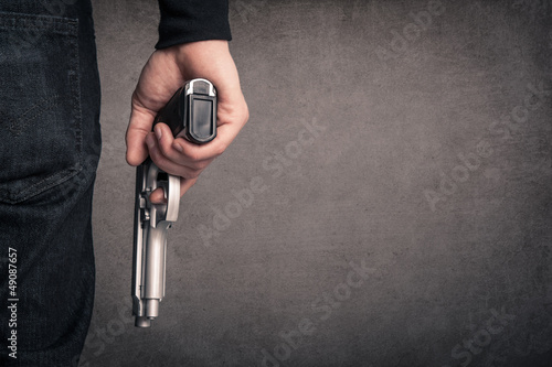 Fotografia Killer with gun close up over grunge background with copyspace.
