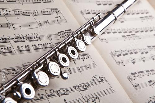 Silver flute on an ancient music score background Fototapeta