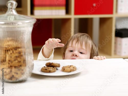 Little boy stealing cookies Fototapeta
