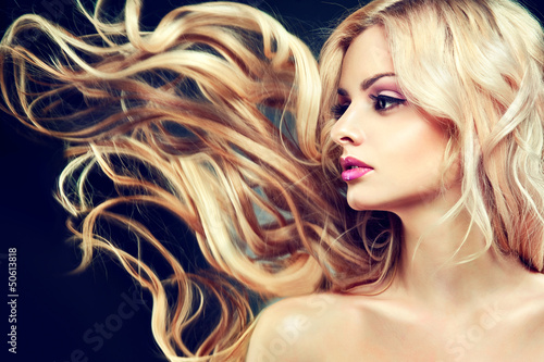 Beautiful model with flying long blonde hair .