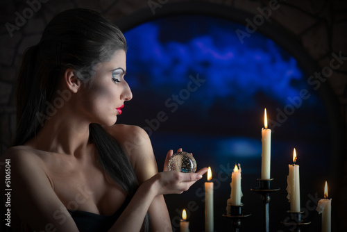 Indoors portrait of a sorceress with glass sphere and candles Fototapeta