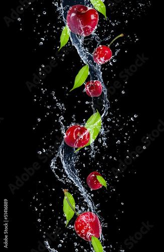 Cherries in water splash, isolated on black background