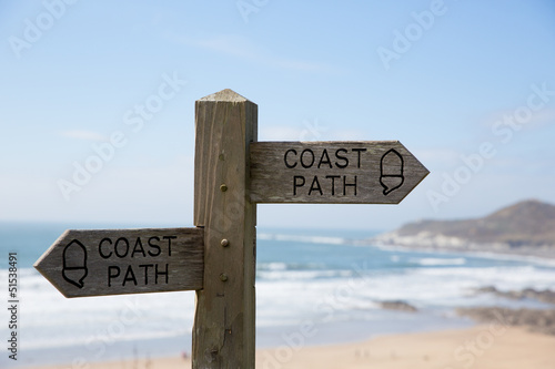 Coast path sign against sea and sand background.