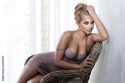 Fototapeta Wspaniała blond dziewczyna pozuje na wiklinowym krześle do pokoju