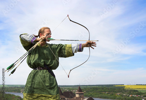 Fototapeta Young archer with bow and arrows in medieval costume aiming