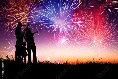Fotografia Szczęśliwa rodzina stojąca na wzgórzu i obserwująca fajerwerki
