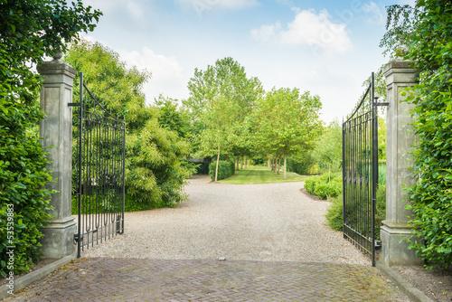 Opened black wrought iron gate of a large estate Fototapeta