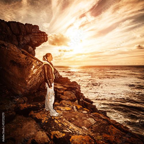 Photographer woman on rocky seashore Wall mural