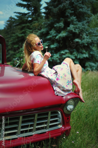 Young woman in vintage dress sitting on a red retro car