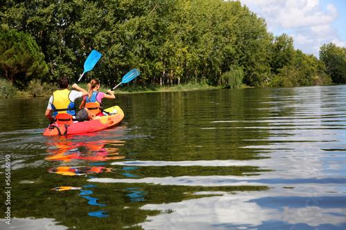 Tableau sur Toile Couple riding canoe in river