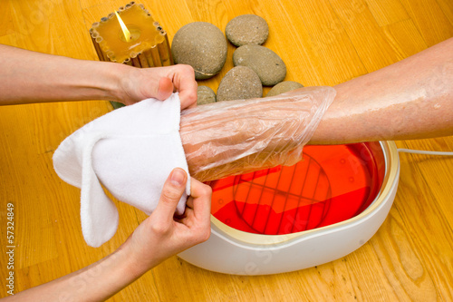 Photo woman foot in paraffin bath at the spa