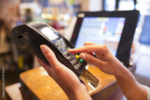 Fotografia Woman hand with credit card swipe through terminal for sale