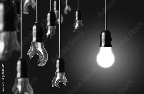 idea concept with broken bulbs and one glowing bulb
