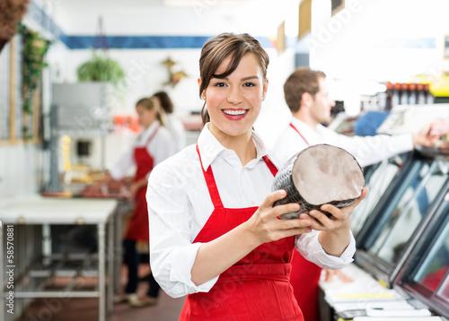 Fotografia Happy Female Butcher Holding Large Ham
