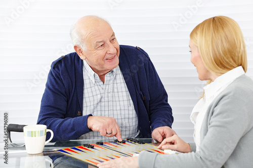 Photographie Woman playing backgammon with senior citizen