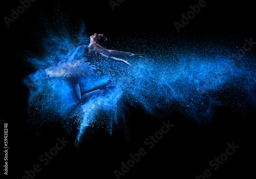 Valokuva Young beautiful dancer jumping into blue powder cloud