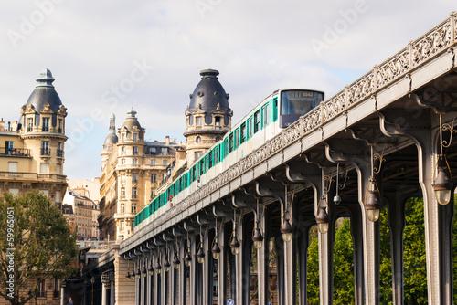 Metro train runs high between buildings, Paris, France. Cityscape in summer. #59965051