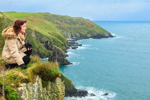 Photo Woman sitting on rock cliff looking to ocean Co. Cork Ireland