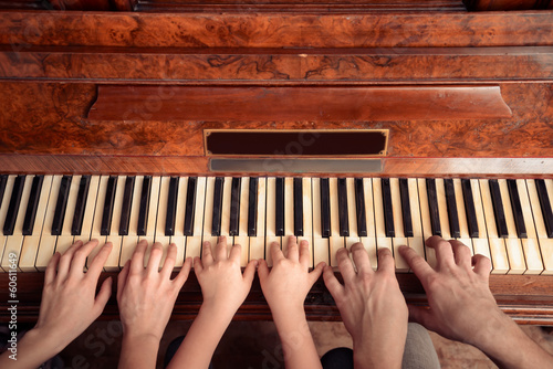 Fotografia Family of three people is playing the piano, front view