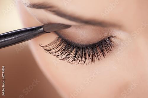Valokuvatapetti Woman applying eyeshadow