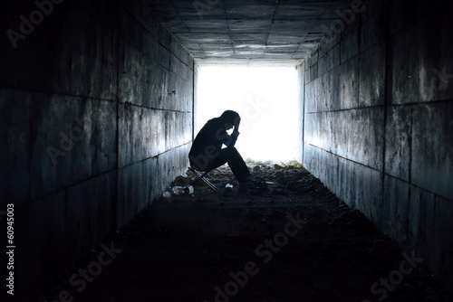 Canvas-taulu depressed man sitting in the tunnel