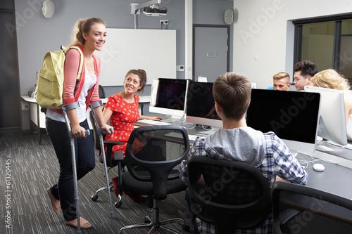 Obraz na płótnie Female Pupil Walking On Crutches In Computer Class