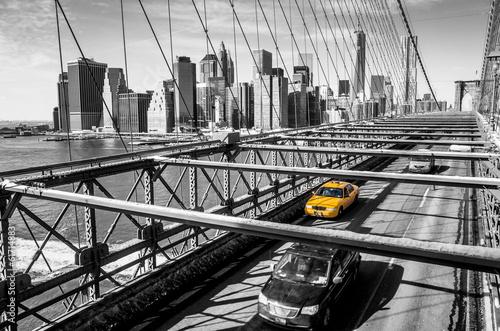 Fototapeta premium Taksówka przejeżdżająca przez Brooklyn Bridge w Nowym Jorku