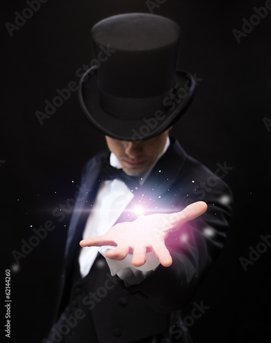 Photo magician holding something on palm of his hand