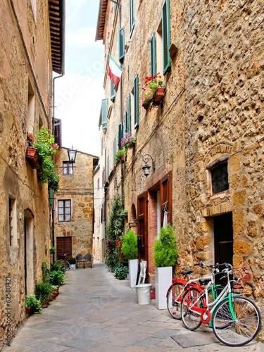 Narrow small town lane in Pienza, Tuscany, Italy with bikes