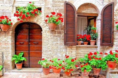 Fototapeta premium Włoski dom przód z kolorowymi doniczkowymi kwiatami