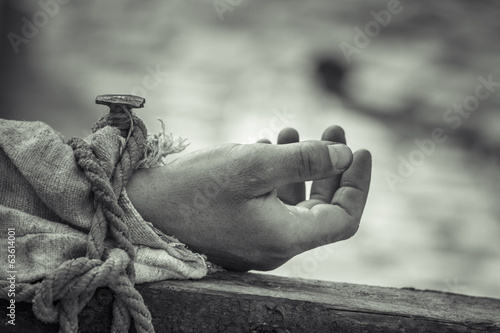 Nailed hand on wooden cross.