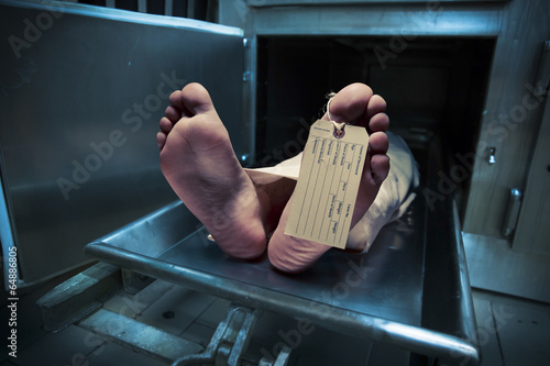 Stampa su Tela Feet on a morgue table with toe tag with dramatic lighting