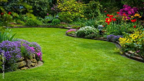 Fototapeta premium Widok na ogród z trawnikiem i sadzeniem