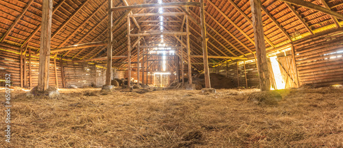 Stampa su Tela Panorama interior of old farm barn with straw