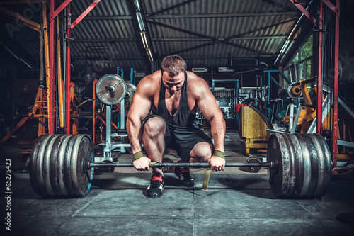 Photographie Powerlifter with strong arms lifting weights