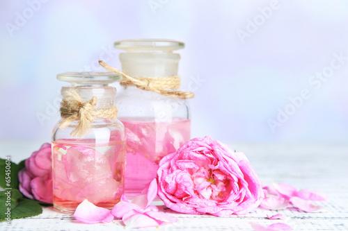 Rose oil in bottles on color wooden table, on light background