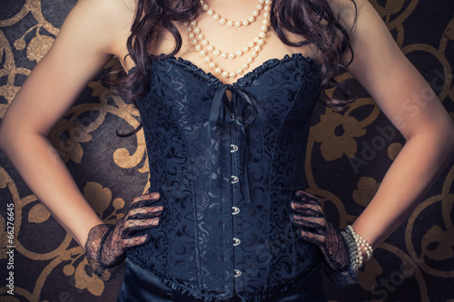 Fotografia woman wearing black corset and pearls against retro background