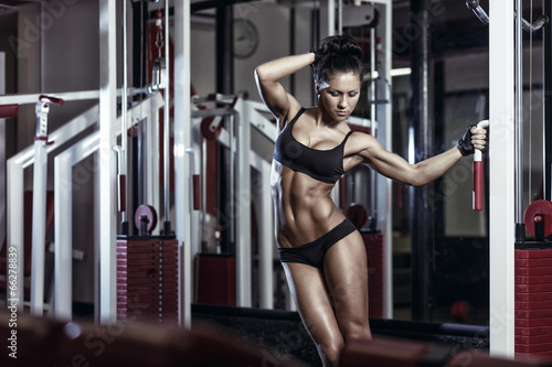 sexy young girl posing in the gym holding on training machine