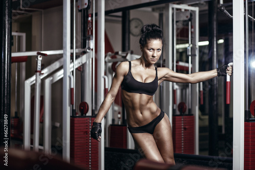 sexy young girl in the gym holding on training machine