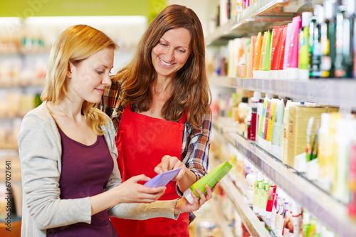 Fotografia Frau neben Verkäuferin vergleicht Produkte in Drogerie