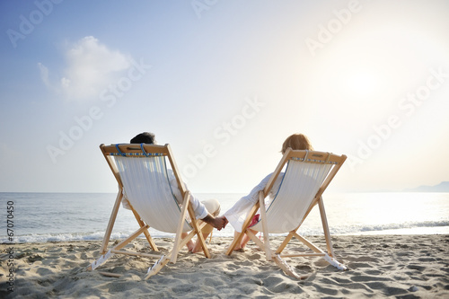 Fotografía romantic couple on deckchair relaxing on the beach