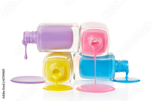 Fotografering Nail polish bottles spilling isolated on white, clipping path